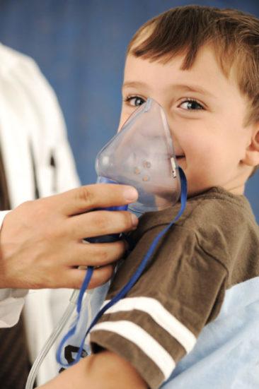 Criança sorrindo fazendo inalação com máscara segurada por médico, possível asma